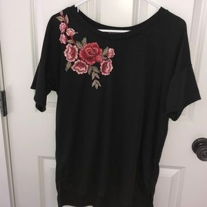 Black T-shirt with floral embroidery.